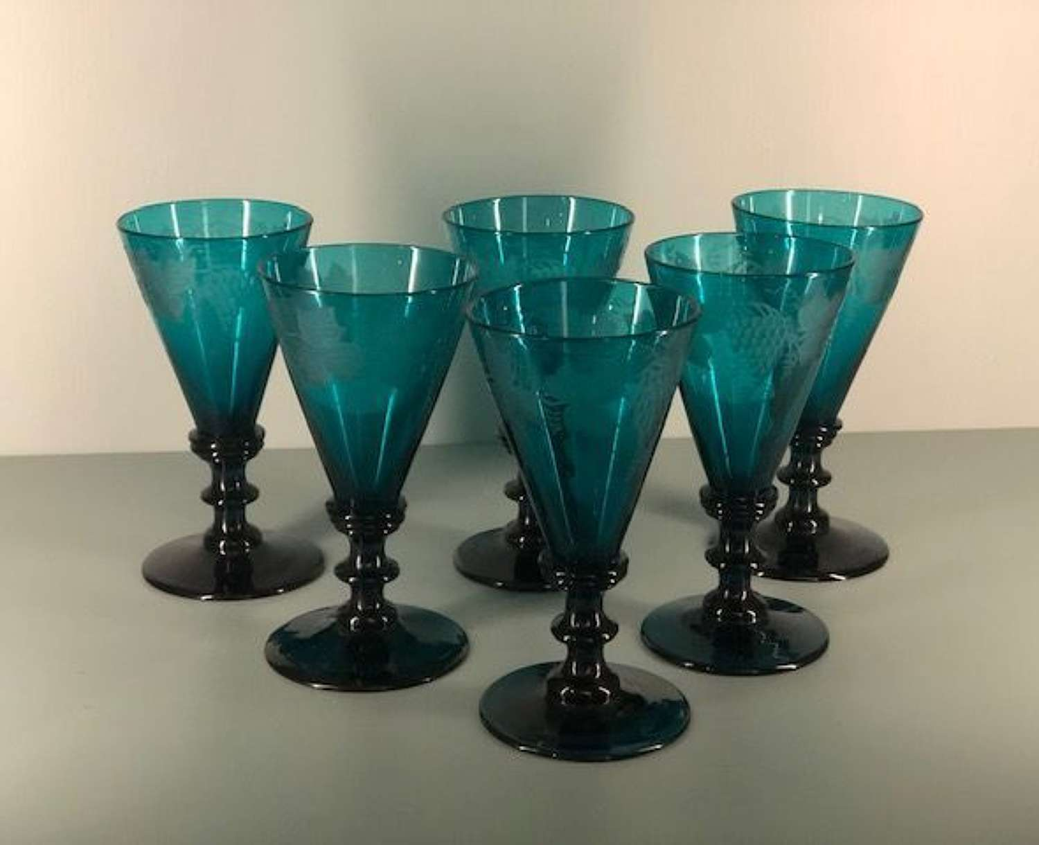 Set of 6 teal green Georgian wine glasses with engraved grape motifs